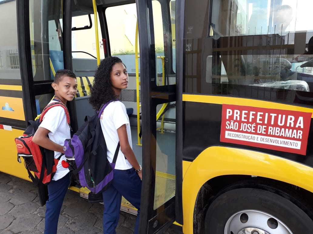 Os alunos Hadassa e Calebe embarcando no ônibus escolar da cidade