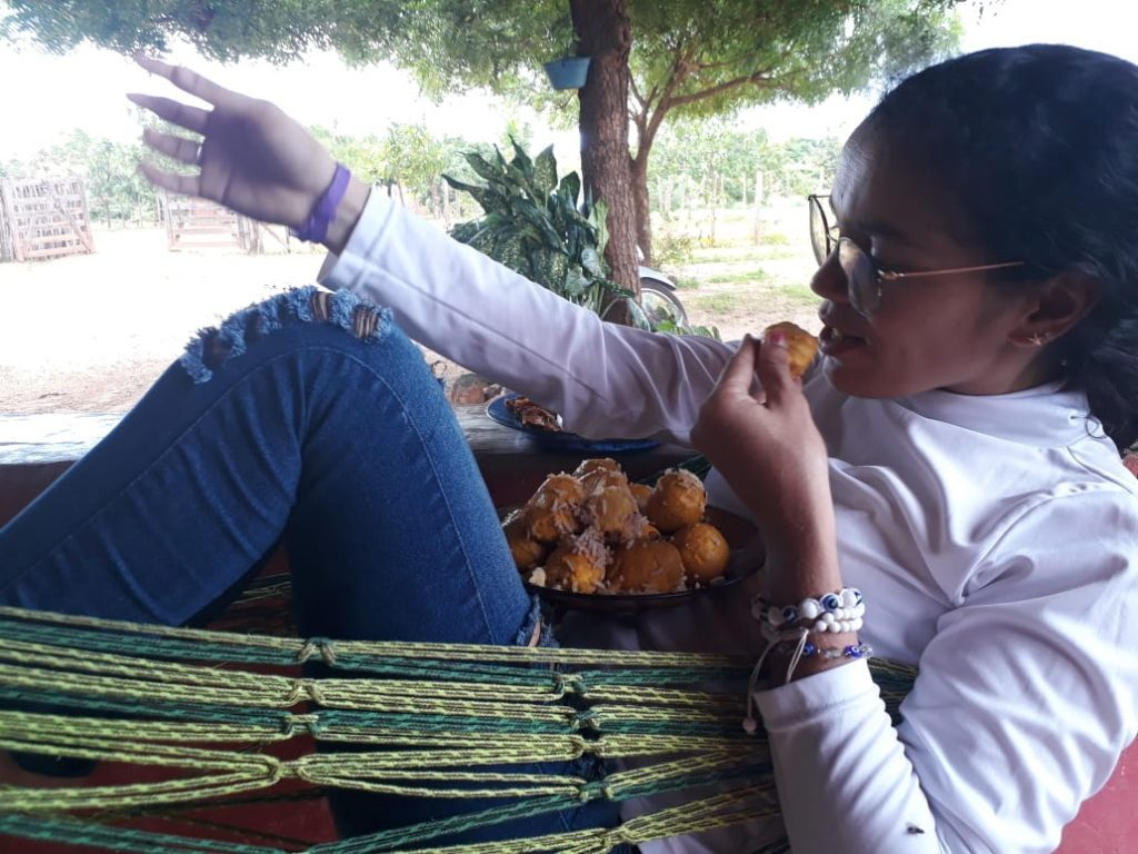 Consuelo prova que não esqueceu as origens e devora um prato de arroz com pequi, na comunidade em que vive, na zona rural de Campo Maior