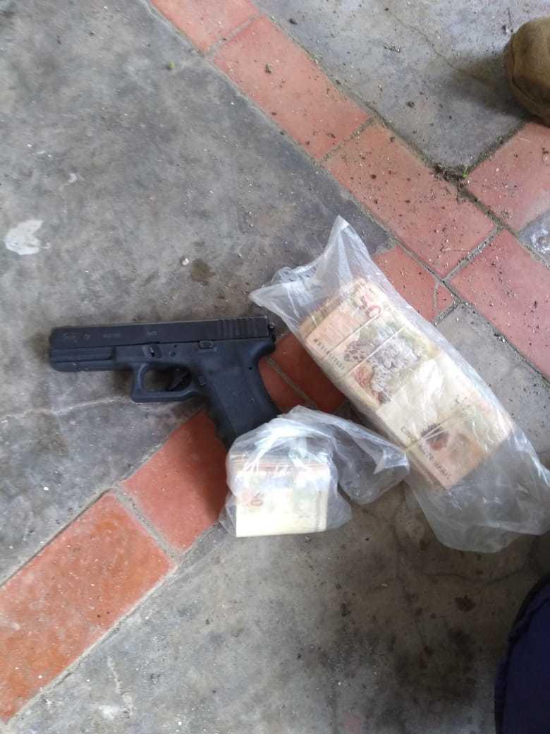 Arma e dinheiro apreendido