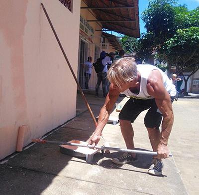 O prefeito ajuda a pintar um prédio público