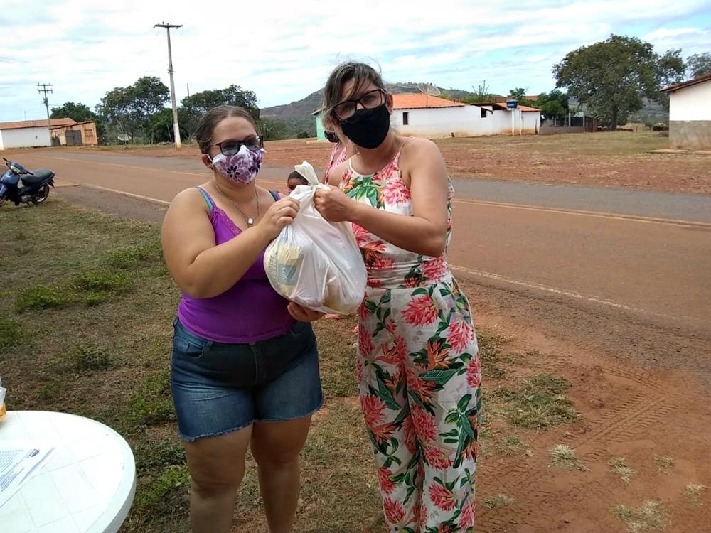 Ao lado direito da imagem, secretária de Educação de Bocaina faz entrega de kit no povoado Barragem