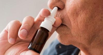Thumb close up old man using nasal spray 850x580
